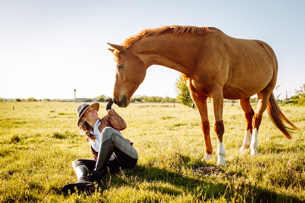 Beautiful young woman in a hat and gloves with a broun horse in a field on a sunset