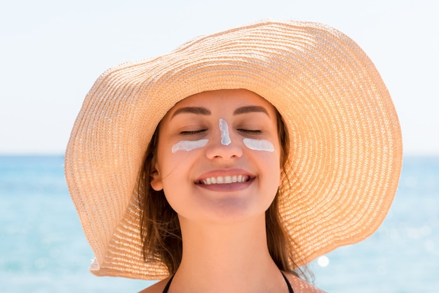 Beautiful young woman in hat is applying sunblock under her eyes and on her nose like indian. sun protection concept