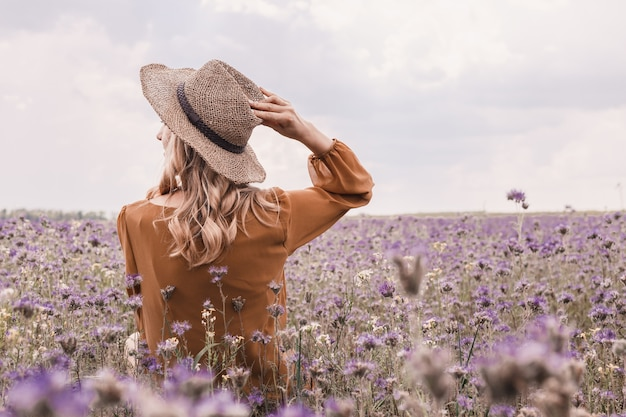 Beautiful young woman in hat in lavender field. blooming flowers