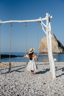 A beautiful young woman in a hat and a light dress is riding on a swing on the ocean shore against the background of huge rocks. tourism and vacation travel.