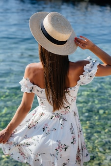 A beautiful young woman in a hat and a light dress with her back is walking along the ocean shore against the background of huge rocks on a sunny day. tourism and vacation travel.