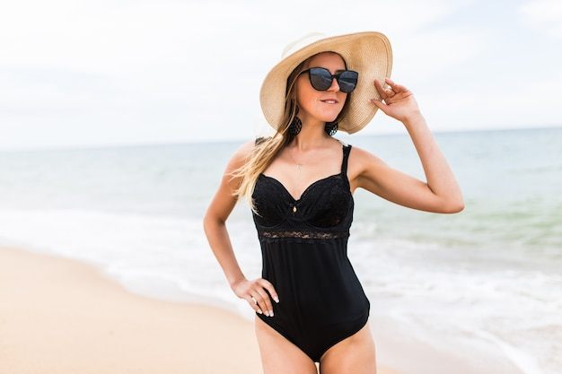 Beautiful young woman in a hat and swimsuit over seaside