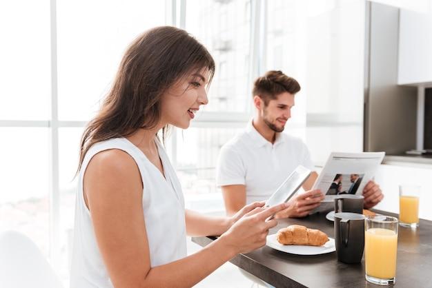 彼女のボーイフレンドがキッチンで新聞を読んでいる間、朝食とタブレットを使用して美しい若い女性
