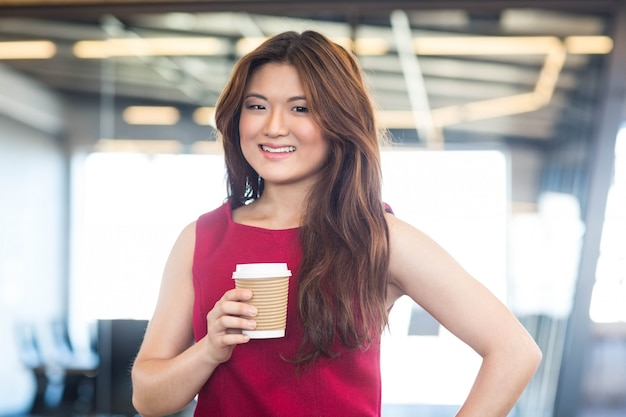 Beautiful young woman having coffee in office