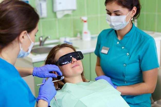 歯科医院で歯科治療を受けている美しい若い女性。アシスタントと女性の歯科医が実際の歯科医院のオフィスでクローズアップ