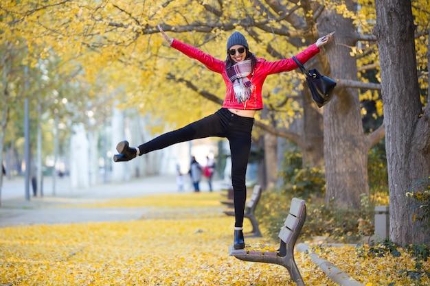 Beautiful young woman having fun in the autumn.