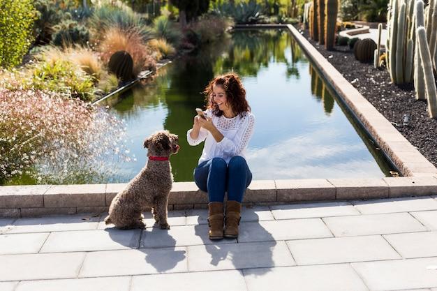 美しい若い女性は彼女のかわいい茶色の犬を楽しんで、携帯電話で写真を撮る。動物のコンセプトが大好きです。屋外