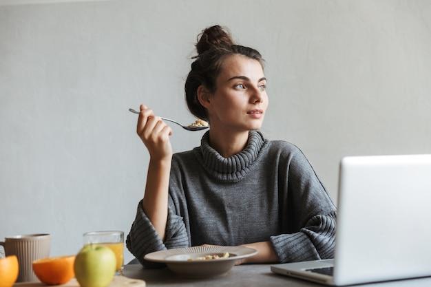 Красивая молодая женщина, имеющая здоровый завтрак, сидя на кухне, используя ноутбук