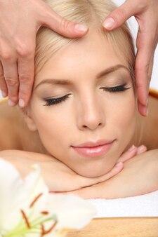 Красивая молодая женщина, имеющая массаж в спа-салоне