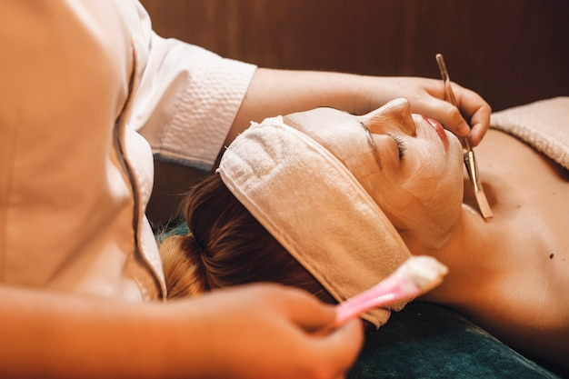 Beautiful young woman having skin care procedures in a wellness spa center.