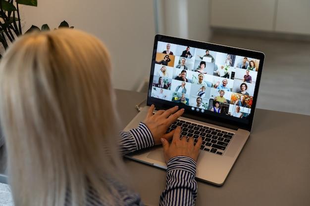 컴퓨터를 통해 화상 회의를 하는 아름다운 젊은 여성. 회의를 호출합니다. 홈 오피스. 코로나바이러스 전염병 동안 집에 있고 집에서 일하는 개념