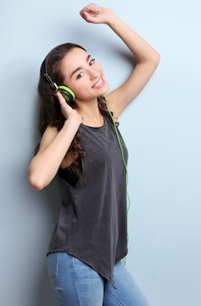 Beautiful young woman in headphones listening to music on light