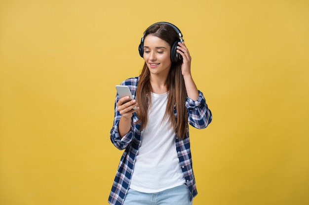 Beautiful young woman in headphones listening to music and singing on yellow background.