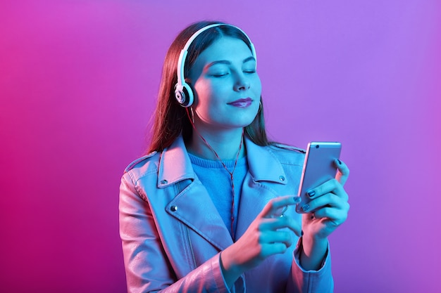 Beautiful young woman in headphones listening to music with closed eyes standing isolated over pink neon space, wearing leather jacket, has long hair