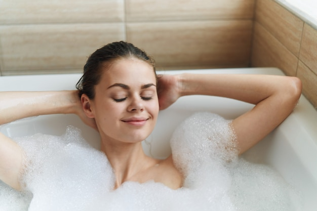 Beautiful young woman in her beautiful snow-white bathtub rests and relaxes, beautiful evidence, bathtub with foam