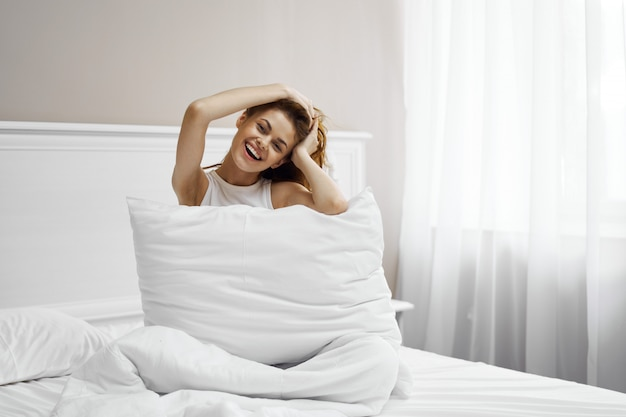 Beautiful young woman in her beautiful snow-white bed relaxes and relaxes, beautiful evidence