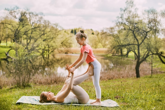 A beautiful young woman and her daughter practice yoga in sportswear while maintaining a healthy lifestyle