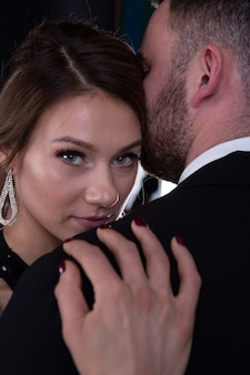 A beautiful young woman hid behind the shoulder of her strong man