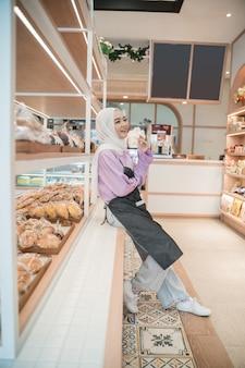 彼女の店で誇らしげに笑っている美しい若い女性ヒジャーブ。魅力的なアジアの若い女性の店主