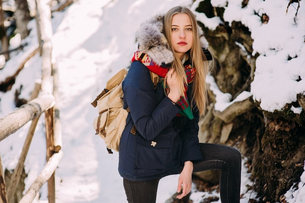 Beautiful young woman on a hike in a winter forest