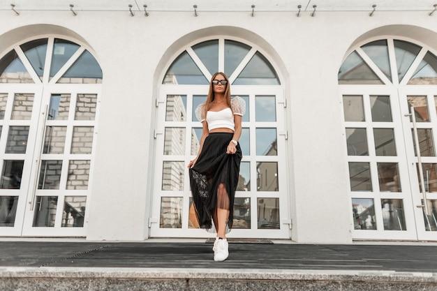 도시에있는 빈티지 건물 근처 포즈를 취하는 가죽 운동화의 트렌디 한 상단에 우아한 검은 색 긴 치마에 선글라스에 아름 다운 젊은 여자 소식통. 매력적인 행복 한 여자는 야외에서 쉬고있다.