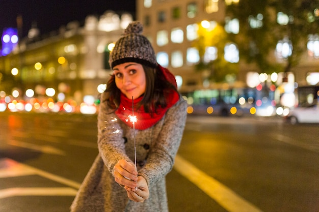 Beautiful young woman hoding a sparkle at night, having fun and smiling