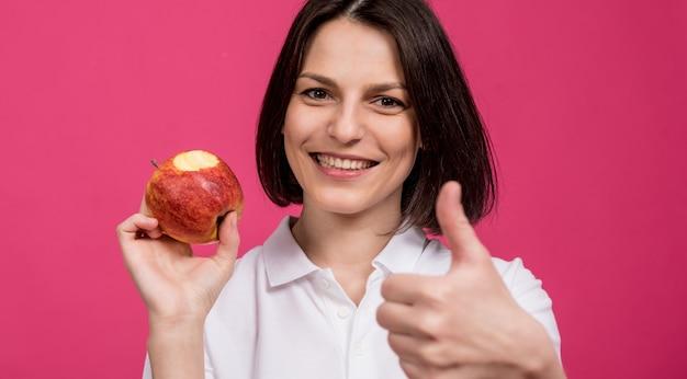 美しい若い女性は彼女の手に大きなリンゴを持っています