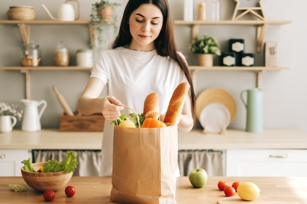 Красивая молодая женщина держит эко хозяйственную сумку со свежими овощами и багетом на кухне.