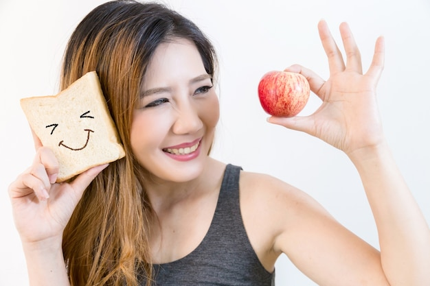 Beautiful young woman hold red apple with smile.