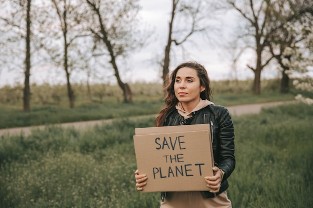 Красивая молодая женщина держит знамя с текстом спасти планету