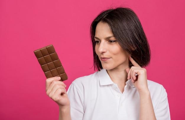 彼女の手にチョコレートのバーを保持している美しい若い女性