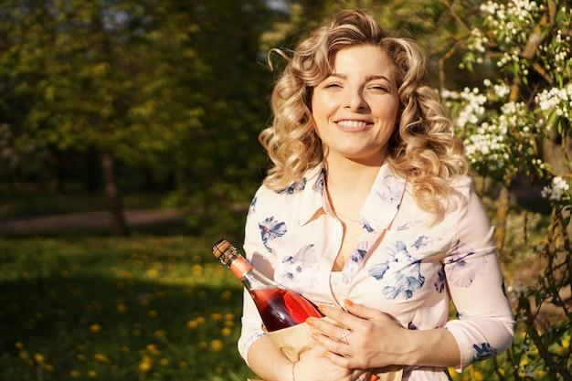 屋外で昼食をとっている間、ワインの空白のボトルを保持している美しい若い女性。緑の芝生のある公園でのピクニック
