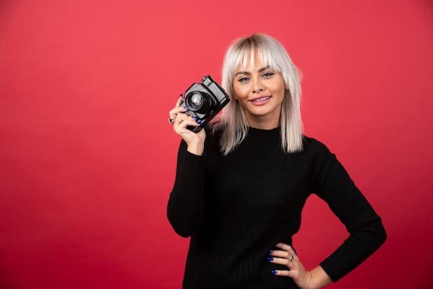 Красивая молодая женщина, держащая камеру, стоя на красном фоне. фото высокого качества