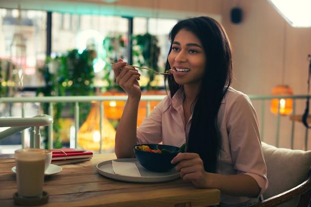 口の近くにフォークを持ち、カフェで昼食をとりながら思いやりのある笑顔で目をそらしている美しい若い女性