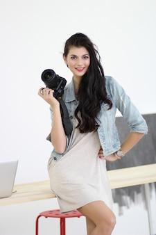 그녀의 손에 전문 카메라를 들고 아름 다운 젊은 여자
