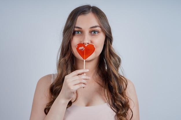 赤いハート型のロリポップを保持している美しい若い女性