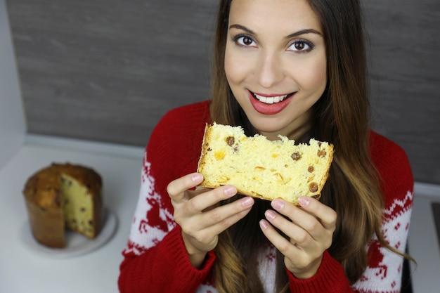 Красивая молодая женщина, держащая кусок панеттоне на рождественские каникулы