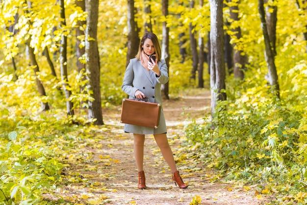 秋の自然の中でスマートフォンを保持している美しい若い女性