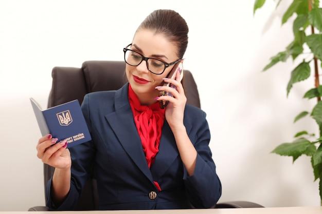 Красивая молодая женщина держит паспорт украины и говорит по телефону в офисе