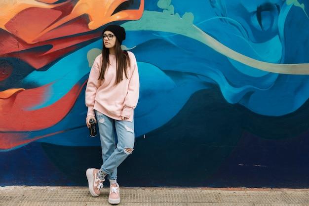 에어로졸을 들고 아름 다운 젊은 여자 다채로운 낙서 벽 앞에 서 있습니다