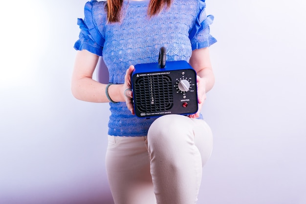 Красивая молодая женщина, держащая машину для производства озона. концепция дезинфекции на белом фоне. covid 19. промышленное оборудование