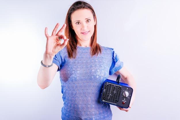 Красивая молодая женщина, держащая машину для производства озона, делая одобренный знак с ее рукой. концепция дезинфекции на белом фоне. covid 19. профессиональное промышленное оборудование