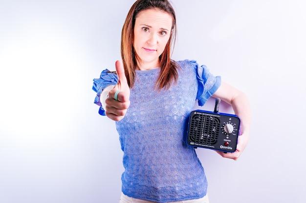Красивая молодая женщина держа машину для производства озона, поднимающую ее большой палец руки. концепция дезинфекции на белом фоне. covid 19. профессиональное промышленное оборудование