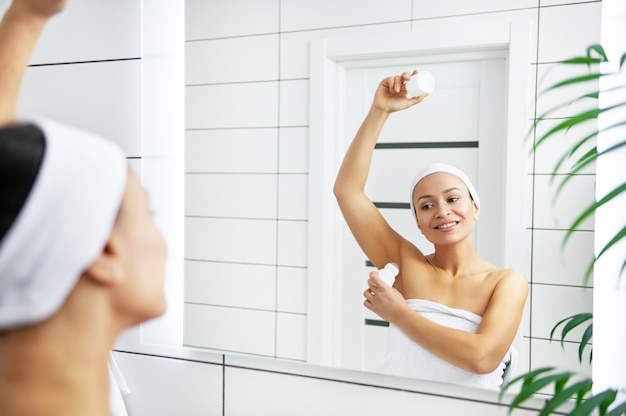Beautiful young woman holding antiperspirant in hand while rolling it on body