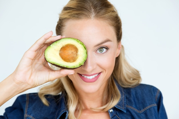 Beautiful young woman holding avocado in the kitchen.