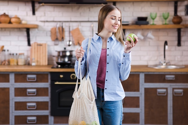 Beautiful young woman holding bag with organic fruits