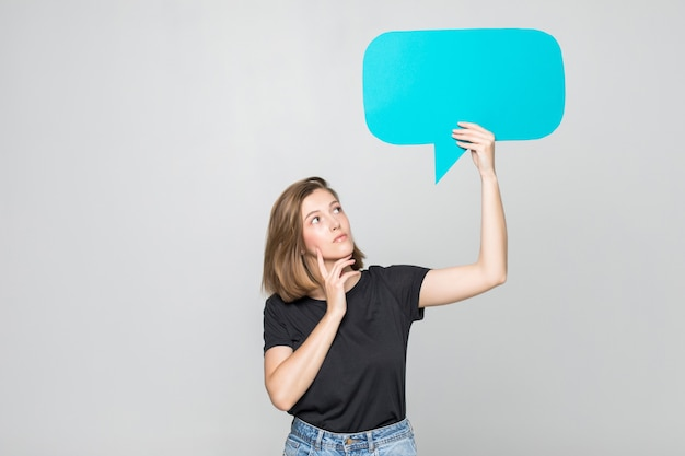 Beautiful young woman holding blank speech bubble over grey