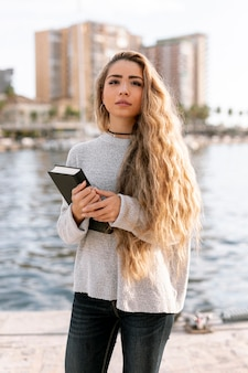 Beautiful young woman holding a book outside