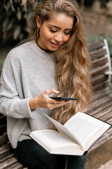 Beautiful young woman holding a book while checking her phone