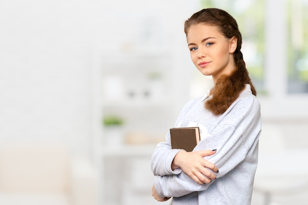 Beautiful young woman holding book